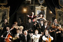 AMADEUS  by Peter Shaffer  director & designer: John Doyle ~Salieri (3rd from left, front row) recounts the premiere of a Mozart opera with (rear centre) Mozart conducting, Constanze singing,Matthew K...