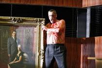 RIGOLETTO   by Verdi   conductor: Martin Andre   director, set & lighting designer: Charles Edwards,tortured Monterone with family portrait: Stephen Richardson (Monterone),Opera North / Leeds, England...