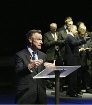 facing the press (at rear): Nicholas Farrell (Tony Blair)in STUFF HAPPENS by David Hare at the Olivier Theatre, National Theatre (NT), London SE1  10/09/2004~design: Christopher Oram  lighting: Paul A...