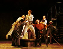 'THE COMEDY OF ERRORS' (Shakespeare)~l-r: Anthony Howell (Antipholus of Ephesus - with sword), Nicholas Khan (Second Merchant, in red shirt), Tom Smith (Dromio of Ephesus, on back)~RSC/RST, Stratford-...