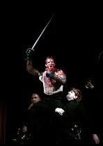 'CORIOLANUS' (Shakespeare)~triumphant and bloodied Coriolanus held aloft: Ralph Fiennes~Almeida Theatre/Gainsborough Studios, London N1  14/06/2000