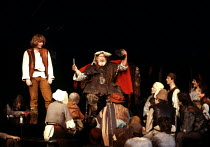 'HENRY IV pt.i' (Shakespeare) in Eastcheap: (left) Gerard Murphy (Hal), (seated) Joss Ackland (Sir John Falstaff) RSC/Barbican Theatre, London EC2 (opening production)    1982