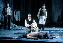 'TIMON OF ATHENS' (Stephen Oliver after Shakespeare)~centre: (lying on stage) Monte Jaffe (Timon), Nicholas Folwell (Mutius)~English National Opera / London Coliseum                    15/05/1991