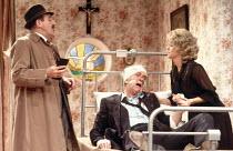 LOOT   by Joe Orton   design: Saul Radomsky   lighting: Mick Hughes   director: Jonathan Lynn   l-r: Leonard Rossiter (Inspector Truscott), Patrick O'Connell (McLeavy), Gemma Craven (Nurse Fay) Amb...