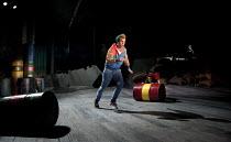 THE COMEDY OF ERRORS   by Shakespeare   design: Jon Bausor   lighting: Jon Clark   director: Amir Nizar Zuabi ~IV/iii: Bruce MacKinnon (Dromio of Syracuse), (behind oil drum) Amie Burns Walker (Courte...