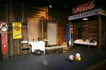 BONNIE AND CLYDE   written & directed by: Linnie Reedman   music & lyrics: Joe Evans   design: Katharine Heath   lighting: Catherine Webb   stage,set,empty,gas,petrol,pump,cigarette,poster,bottles,be...
