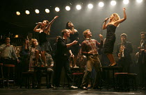 THE COMMITMENTS   by Roddy Doyle   design: Soutra Gilmour   lighting: Jon Clark   choreography: Ann Yeedirector: Jamie Lloyd ~foreground centre: Killian Donnelly (Deco)   on tables, l-r: Sarah O'Conno...