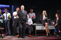 GREAT BRITAIN   by Richard Bean   design: Tim Hatley   lighting: Neil Austin   director: Nicholas Hytner   the proprietor holds forth: Dermot Crowley (Paschal O'Leary)   sitting on table: Lucy Punch...