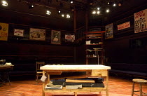 PLAY MAS   by Mustapha Matura   design: Libby Watson   lighting: Mark Jonathan   director: Paulette Randall   stage,set,empty,tailor,shop,table,cutting,cloth,fabric,poster, Orange Tree Theatre, Richmo...