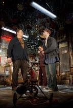 AMERICAN BUFFALO   by David Mamet   design: Paul Wills   lighting: Mark Henderson   director: Daniel Evans ~l-r: John Goodman (Don Dubrow), (rear) Damian Lewis (Walter 'Teach' Cole), Tom Sturridge (Bo...
