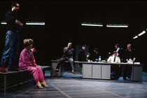 MURMURING JUDGES   by David Hare   design: Bob Crowley   lighting: Mark Henderson   director: Richard Eyre ~police station - left, in pink: Judith Coke (Woman under arrest)   sitting on desk, pointing...