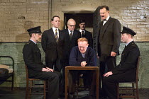 HANGMEN   by Martin McDonagh   design: Anna Fleischle   lighting: Joshua Carr   director: Matthew Dunster coming for the condemned man - 2nd left: Reece Shearsmith (Syd)   seated: Josef Davies (Hennes...