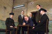 HANGMEN   by Martin McDonagh   design: Anna Fleischle   lighting: Joshua Carr   director: Matthew Dunster coming for the condemned man - centre, l-r: Reece Shearsmith (Syd), Josef Davies (Hennessy), S...