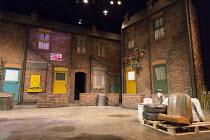 ANITA AND ME   by Meera Syal   adapted for the stage by Tanika Gupta   design : Bob Bailey   lighting: Chahine Yavroran   director: Roxana Silbert   stage,set,exterior,house,windows,junk,rubbish,car s...