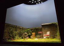 ESCAPED ALONE by Caryl Churchill design: Miriam Buether lighting: Peter Mumford director: James Macdonald stage,set,full,empty,garden,grass,plants,fence,chairs,shed,exterior,outdoors,proscenium,lights...