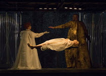 Queen Tye and the Scribe leave the body of Akhnaten: Rebecca Bottone (Queen Tye), Anthony Roth Costanzo (Akhnaten), Zachary James (Scribe) in AKHNATEN by Philip Glass opening at English National Opera...