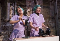 factory work - l-r: Alice Hewkin (Xiaomei), Rebecca Boey (Sange) in THE SUGAR-COATED BULLETS OF THE BOURGEOISIE by Anders Lustgarten opening at the Arcola Theatre, London E8 on 12/04/2016   co-product...