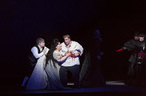 Act 2 - Tristan wounded, l-r: Craig Colclough (Kurwenal), Heidi Melton (Isolde), Stuart Skelton (Tristan), (far right) Stephen Rooke (Melot) in TRISTAN AND ISOLDE by Wagner opening at English National...