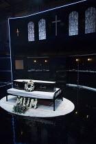 LOOT by Joe Orton  design: Gabriella Slade  lighting: Elliot Griggs  director: Michael Fentiman  stage,set,empty,interior,funeral parlour,coffin,flowers,bouquet,cross,dark,black   Park Theatre, London...