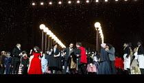 Act 2, Paris at night - front left: Simona Mihai (Musetta - in red dress)  centre: Florian Sempey (Schaunard), Mariusz Kwiecien (Marcello)   right: Nicole Car (Mimi), Michael Fabiano (Rodolfo - kissin...