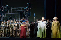front left: Musa Ngqungwana (Amonasro - in cage, reaching out), Latonia Moore (Aida)  right: Robert Winslade Anderson (Ramfis - with spear), Matthew Best (The King of Egypt), Michelle DeYoung (Amneris...