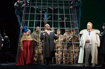 l-r: Latonia Moore (Aida), Musa Ngqungwana (Amonasro - in cage), Robert Winslade Anderson (Ramfis), Matthew Best (The King of Egypt) in AIDA by Verdi opening at English National Opera (ENO), London Co...