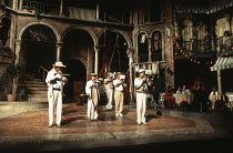 THE VENETIAN TWINS by Carlo Goldoni in a new version by Ranjit Bolt design: Kendra Ullyart lighting: Chris Ellis fights: Malcolm Ranson director: Michael Bogdanov <br> opening sequence: street musicia...