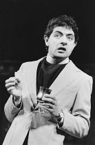 THE NEW REVUE written by Richard Curtis, Ben Elton & Rowan Atkinson music: Howard Goodall design: Will Bowen lighting: Mark Henderson <br> Rowan Atkinson Shaftesbury Theatre, London WC1 07/03/1986 (c)...