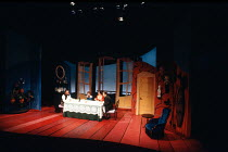 at the table, l-r: Terence Rigby (Captain Perella), (Nono, the son), Marion Bailey (Mrs Perella), Trevor Eve (Paolino) in MAN, BEAST AND VIRTUE by Luigi Pirandello at the Cottesloe Theatre, National T...