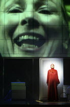 Stephanie Marshall (Offred) with a projected image of Aunt Lydia (Helen Field) in THE HANDMAID'S TALE at English National Opera (ENO), London Coliseum, London WC2 03/04/2003 music: Poul Ruders librett...