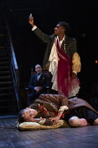 'The Murder of Gonzago' - Ashley G Gayle (Player) prepares to poison Nick Howard-Brown (Player King), watched by Jonathan Hyde (Claudius) in HAMLET by Shakespeare opening at the Theatre Royal Windsor,...